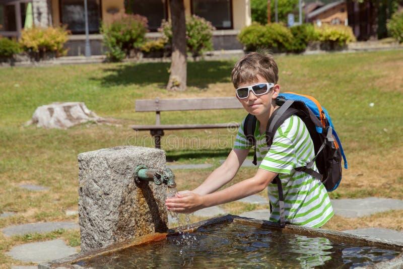 o menino novo é água potável de uma fonte foto de stock