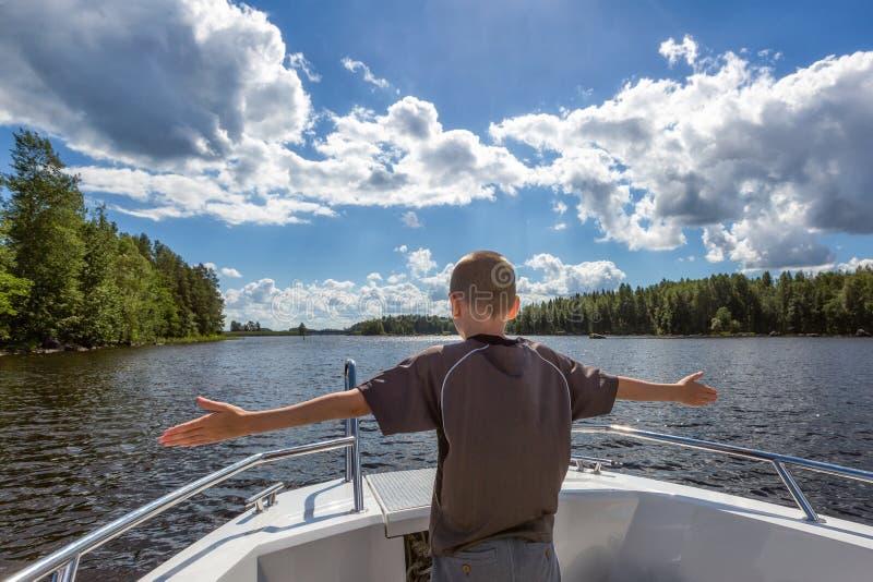 O menino novo aprecia uma viagem em um barco de motor fotos de stock royalty free