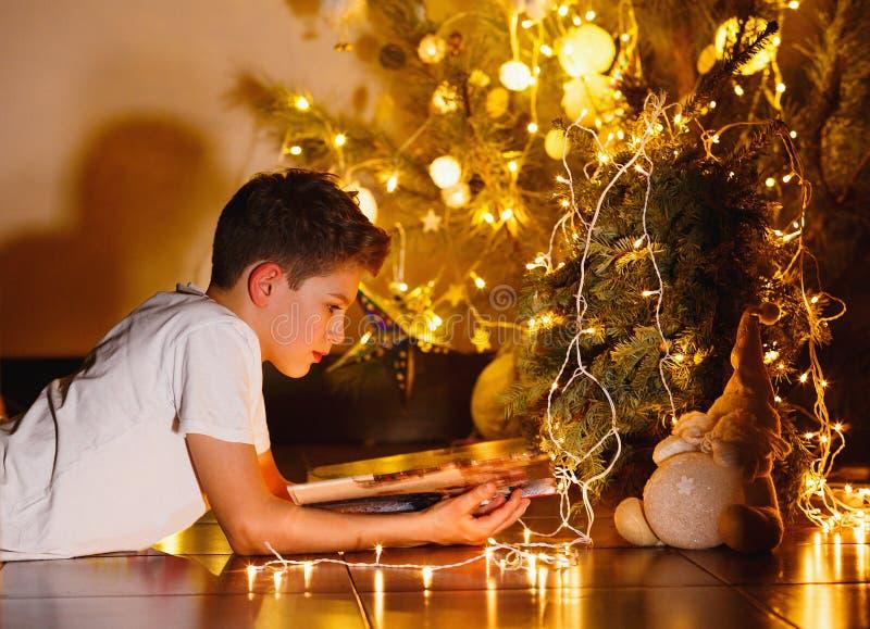 O menino novo bonito na camisa branca de t lê o livro na noite em casa na frente da árvore de abeto com luzes Feriados de inverno imagens de stock