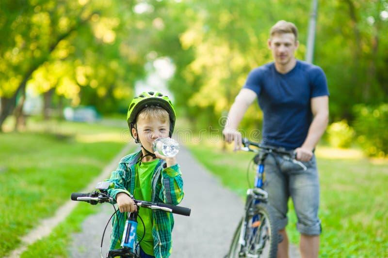 o menino novo com uma garrafa da água está aprendendo montar uma bicicleta com seu pai imagem de stock