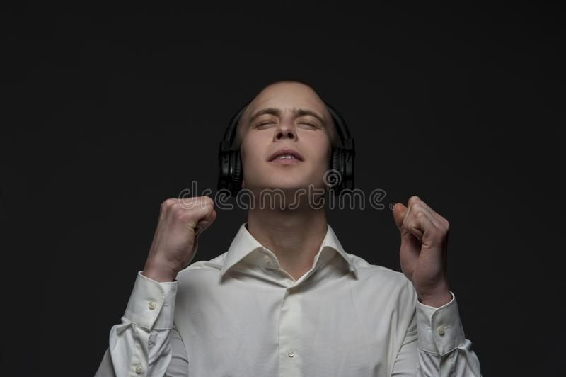 O menino novo do estudante escuta uma música fotografia de stock