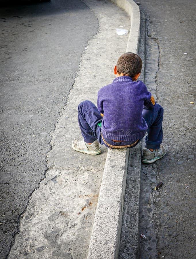O menino novo em uma camiseta roxa e na calças de ganga senta-se na beira da rua fotos de stock royalty free