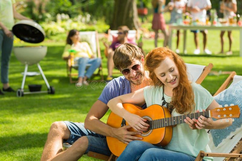 O menino novo ensina o jogo da guitarra imagens de stock royalty free