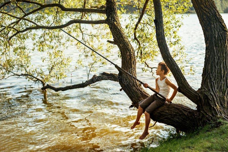 O menino novo está pescando ao sentar-se em um ramo de árvore sobre um rio imagens de stock royalty free