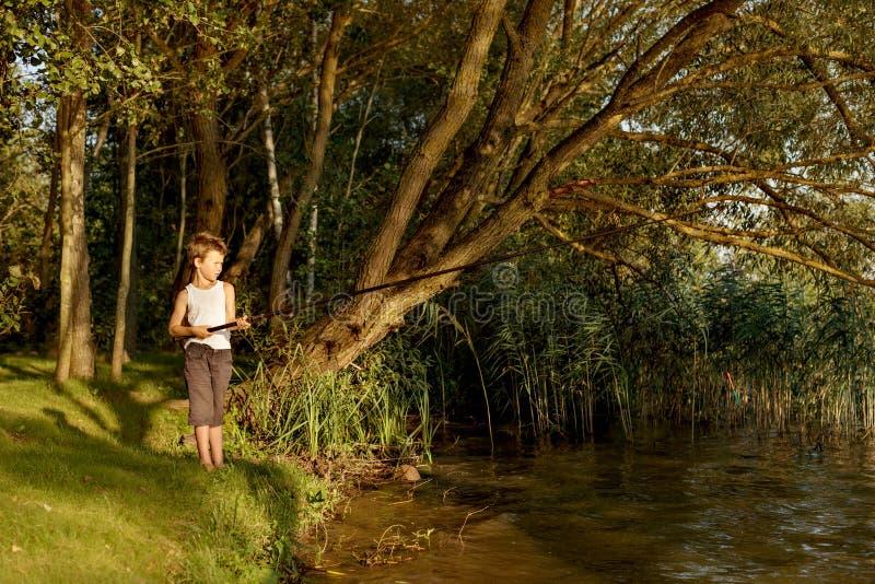 O menino novo está pescando em um rio imagem de stock royalty free
