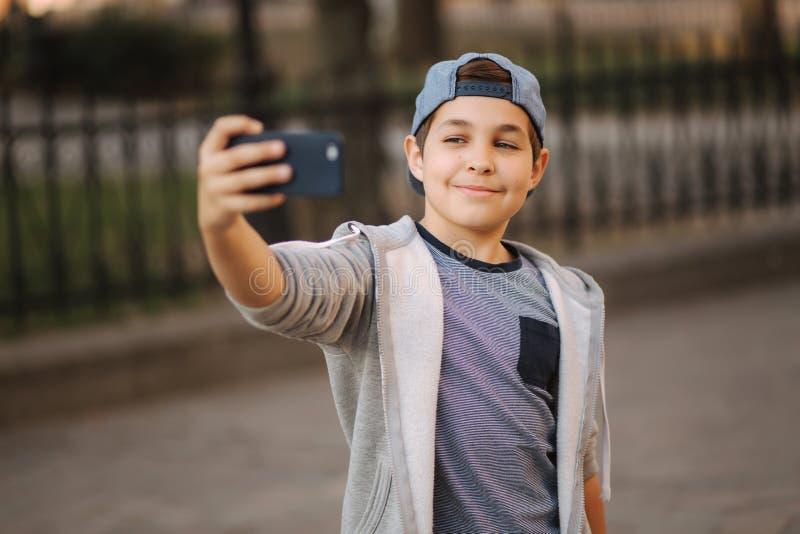 O menino novo faz um selfie no smartphone no centro da cidade Menino bonito no chapéu azul Menino de escola à moda fotografia de stock