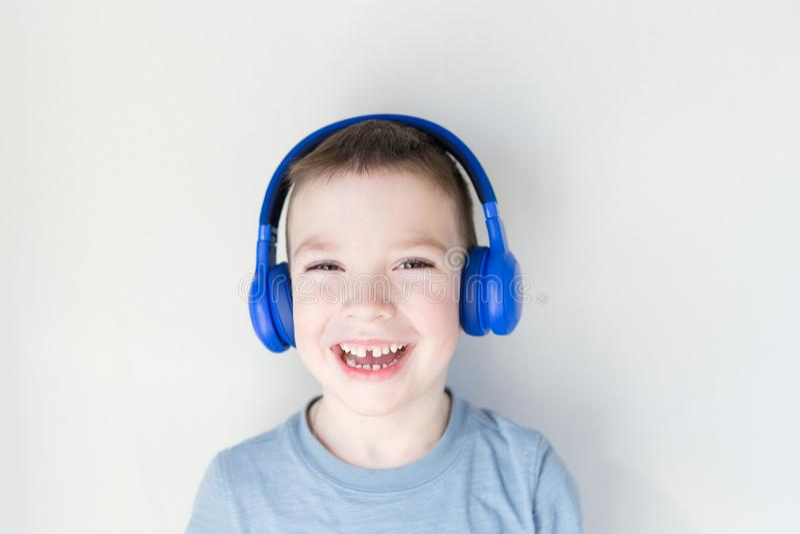 O menino novo feliz é de sorriso e de escuta a música nos fones de ouvido azuis, estando na frente da parede branca Copie o espa? fotos de stock royalty free