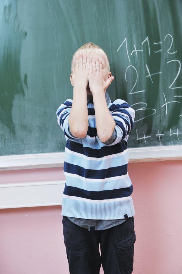 O menino novo feliz na matemática da primeira classe classifica foto de stock royalty free