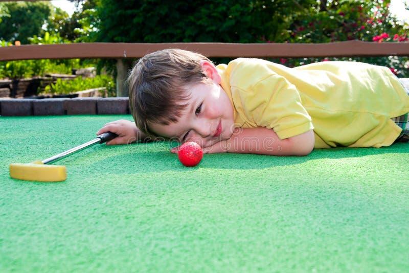 O menino novo joga o mini golfe fotografia de stock royalty free