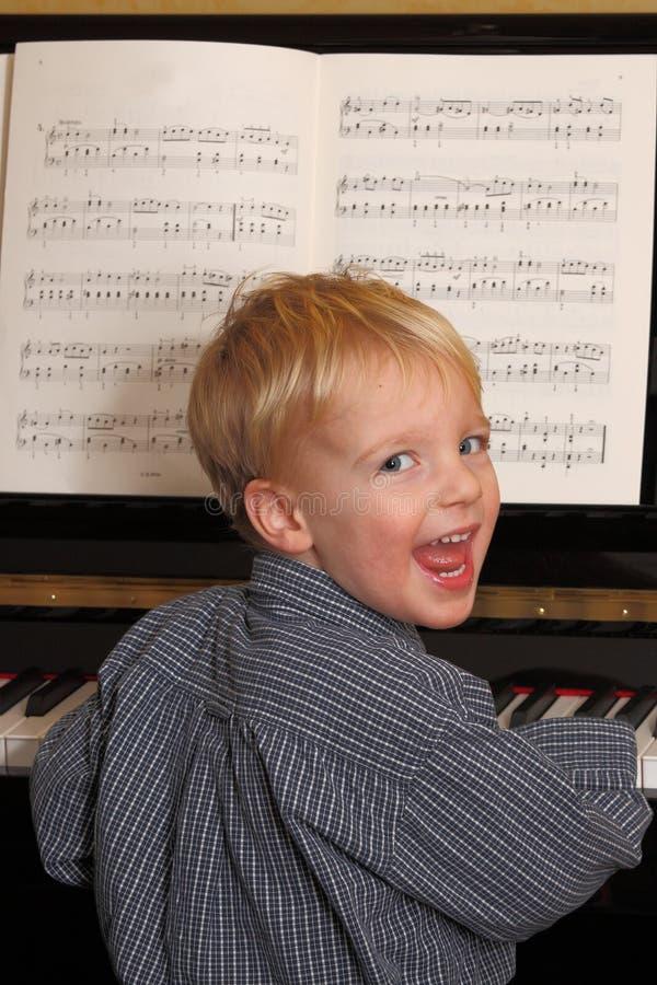 O menino novo joga o piano imagens de stock royalty free
