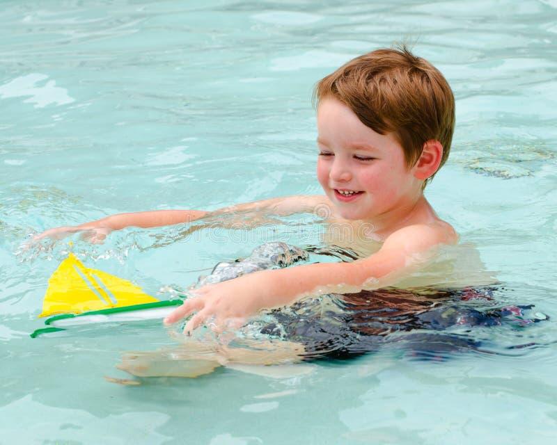O menino novo jogar com barco do brinquedo quando na associação fotografia de stock royalty free