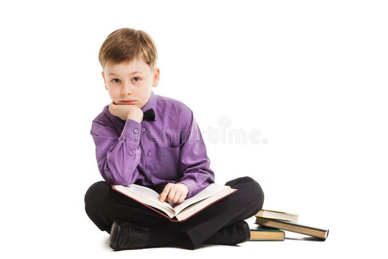 O menino novo lê um livro isolado imagem de stock royalty free