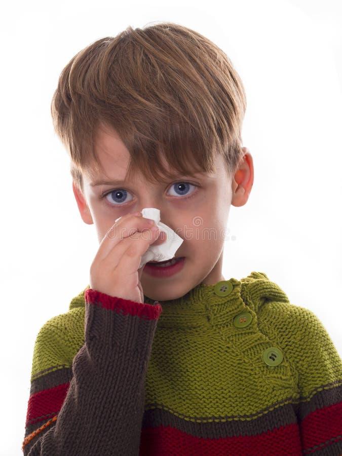 O menino novo limpa um nariz com o guardanapo fotos de stock royalty free