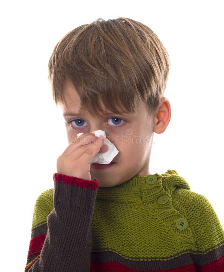 O menino novo limpa um nariz com o guardanapo foto de stock