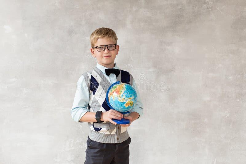 O menino novo na camiseta branca e na calças preta mantém o globo nas mãos e o levantamento contra a parede cinzenta imagens de stock