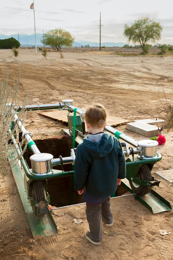 O menino novo olha para baixo em uma sepultura aberta em Dusty Desert Cemete imagem de stock