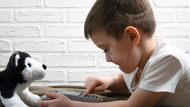 O menino novo que encontra-se no assoalho que pressiona o terminal da posição abotoa-se Tecnologias modernas para crianças Prátic fotos de stock royalty free