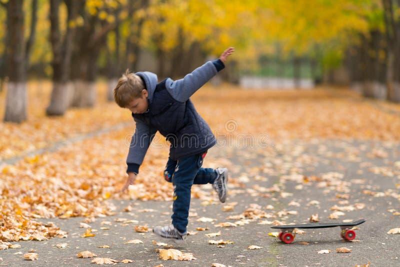 O menino novo salta fora de seu skate fotos de stock
