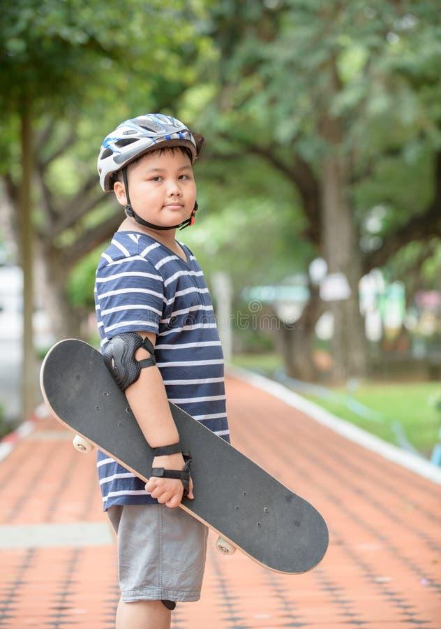 O menino obeso aprende montar a placa do patim imagens de stock royalty free