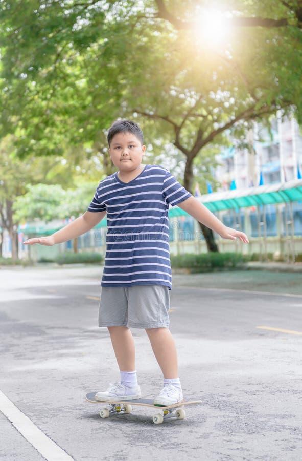 O menino obeso aprende montar a placa do patim no parque da aptidão imagens de stock