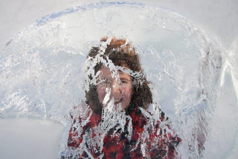 O menino olha através da escultura de gelo foto de stock