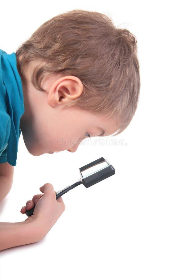 O menino olha através do magnifier imagens de stock