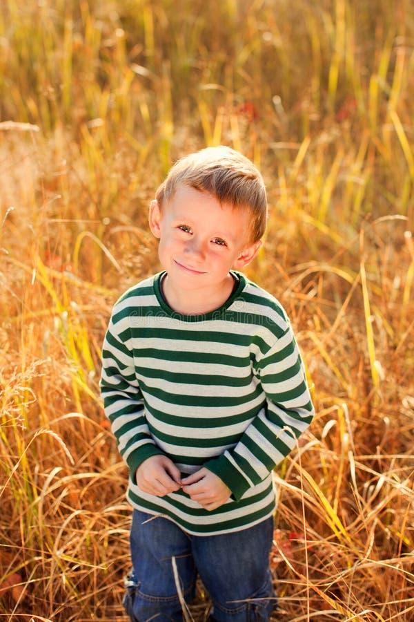 O menino olha a câmera imagem de stock