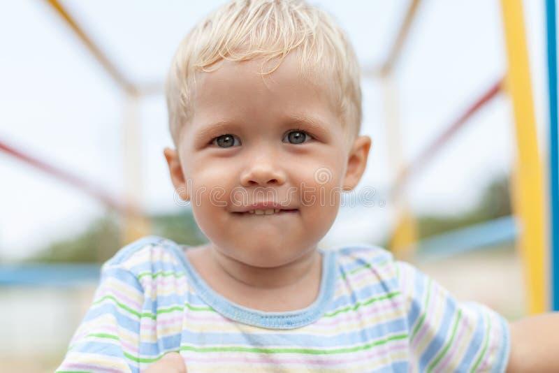 O menino olha a câmera que morde seu bordo com profundidade de campo estreita imagens de stock