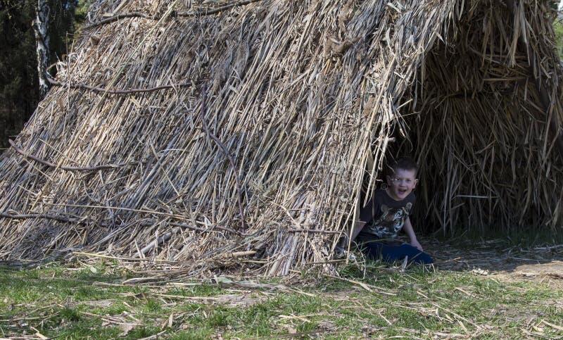 O menino olha fora da barraca da palha imagem de stock royalty free