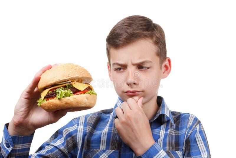 O menino olha um cheeseburger e um pensamento fotos de stock royalty free