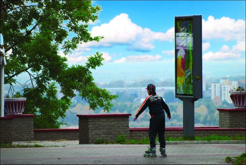 O menino patina em rolo-skateres abaixo da rua na mola fotografia de stock