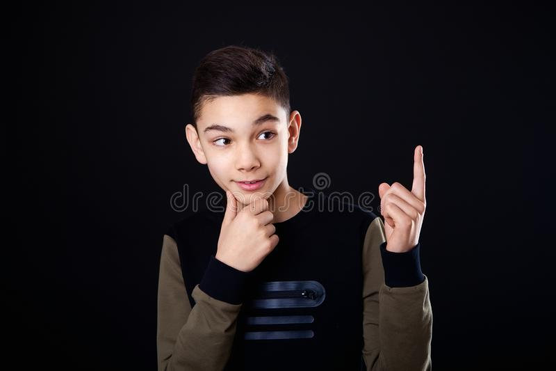 O menino pensa pensamentos O indivíduo mostra um dedo acima, uma ideia Lugar para o texto Fundo preto, estúdio, isolado fotografia de stock