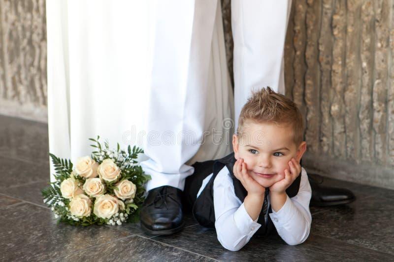 O menino pensativo pequeno encontra-se em um assoalho com um ramalhete nupcial em um casamento imagem de stock