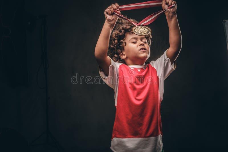O menino pequeno bonito do campeão no sportswear põe sobre a medalha de ouro em um fundo textured escuro imagem de stock royalty free