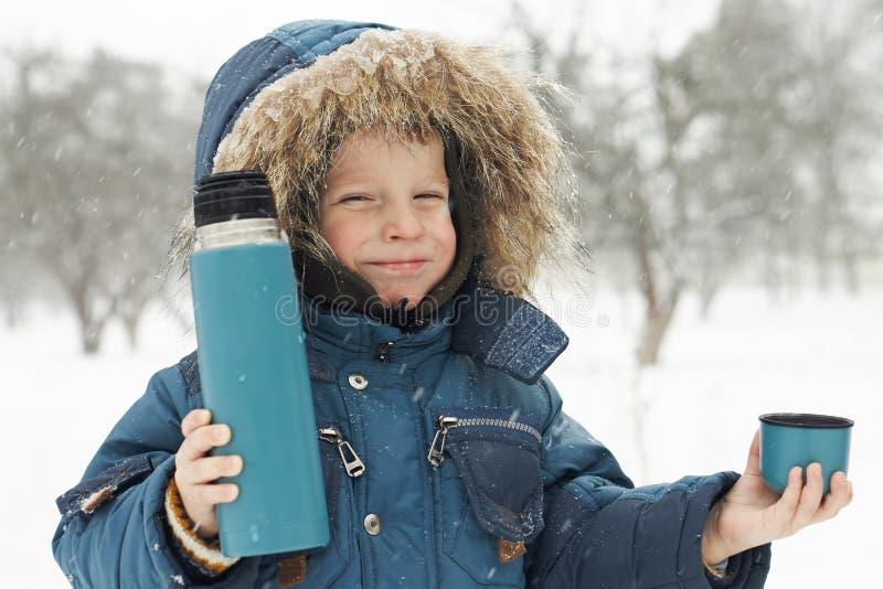 O menino pequeno engraçado convida para beber o chá quente do thermos foto de stock royalty free