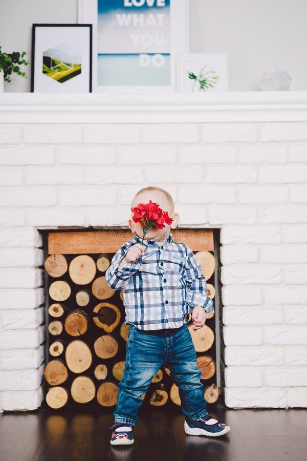 O menino pequeno, engraçado um ano de nascimento realiza em suas flores artificiais vermelhas das mãos no fundo de uma chaminé imagens de stock royalty free