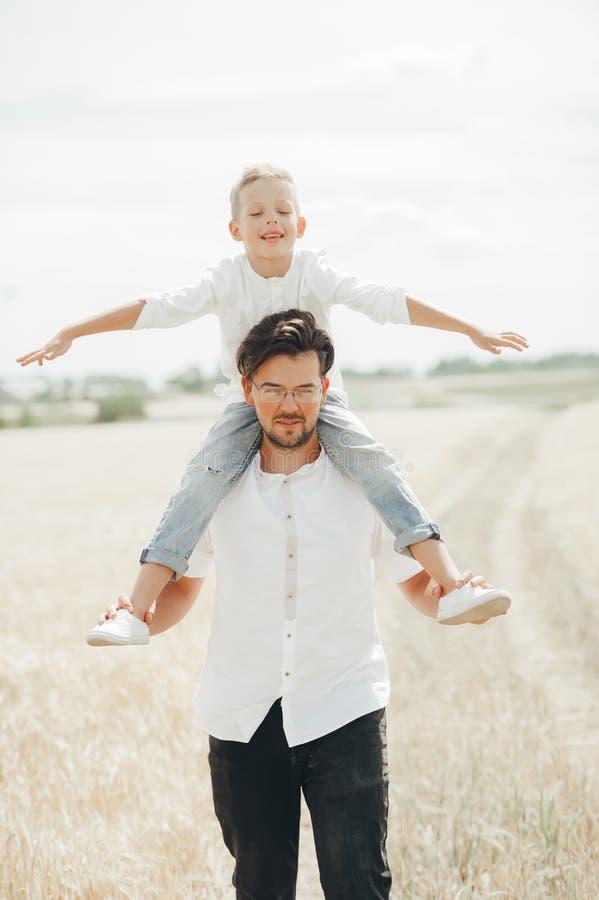 O menino pequeno está sentando-se em seus ombros a do pai no campo de trigo fotos de stock
