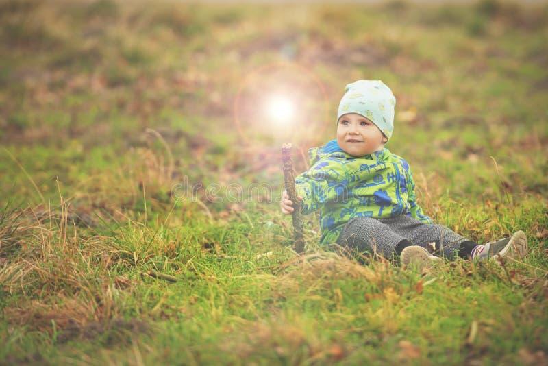 O menino pequeno est? sentando-se na grama e est? guardando-se a varinha m?gica com luz fora dela fotos de stock royalty free