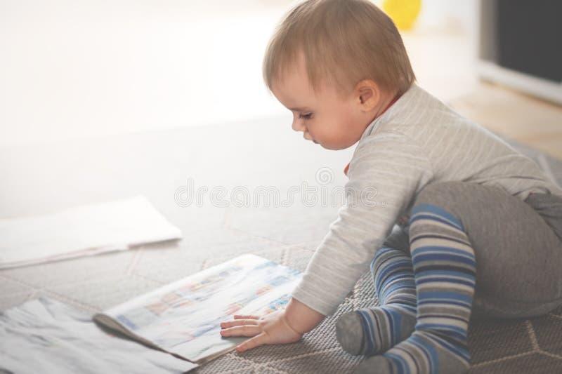 O menino pequeno est? sentando-se no assoalho e est? lendo-se compartimentos foto de stock royalty free