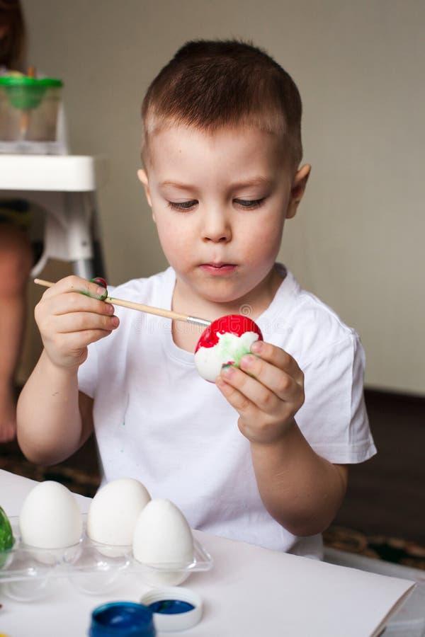 O menino pinta ovos com tinturas - artigos feitos à mão da Páscoa, faculdade criadora do ` s das crianças, desenvolvimento, trein fotografia de stock