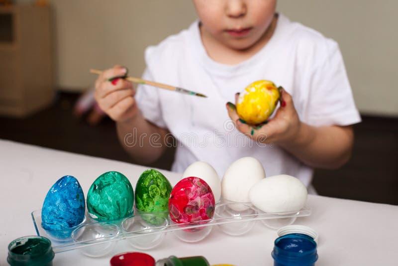 O menino pinta ovos com tinturas - artigos feitos à mão da Páscoa, faculdade criadora do ` s das crianças, desenvolvimento, trein fotos de stock