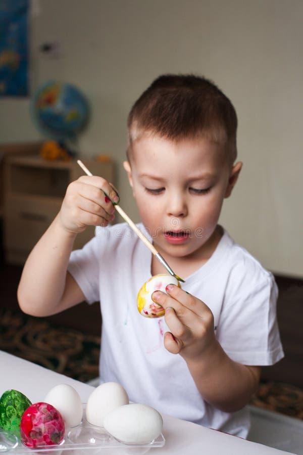 O menino pinta ovos com tinturas - artigos feitos à mão da Páscoa, faculdade criadora do ` s das crianças, desenvolvimento, trein foto de stock royalty free