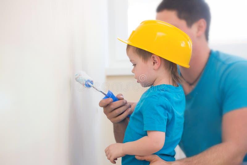 O menino pintou a parede com seu pai fotografia de stock