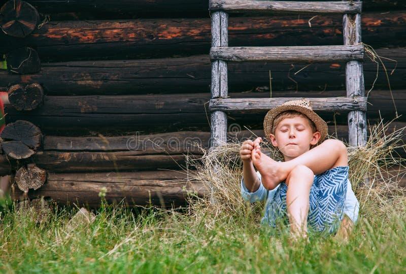 O menino preguiçoso encontra-se na grama sob o celeiro - verão descuidado na contagem fotos de stock