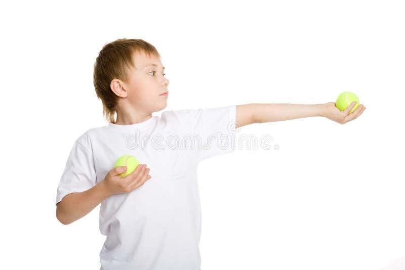 O menino prende esferas de tênis. imagem de stock