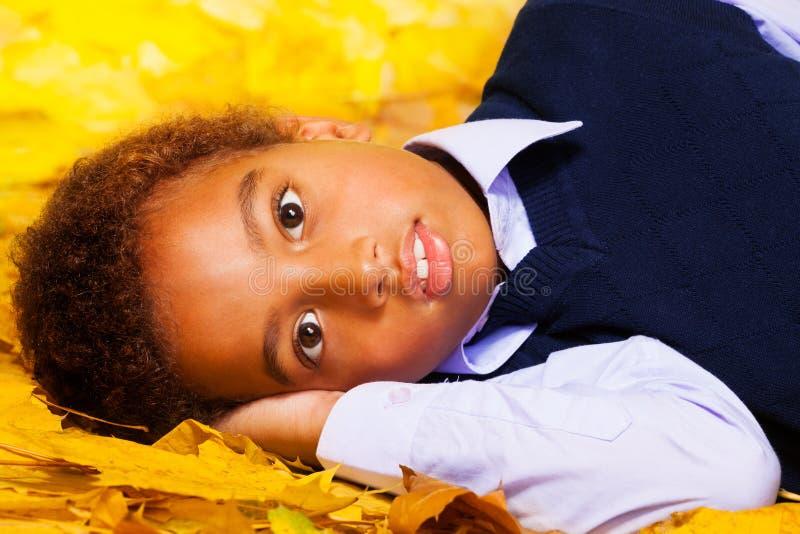 O menino preto pequeno coloca nas folhas de bordo do outono fotos de stock
