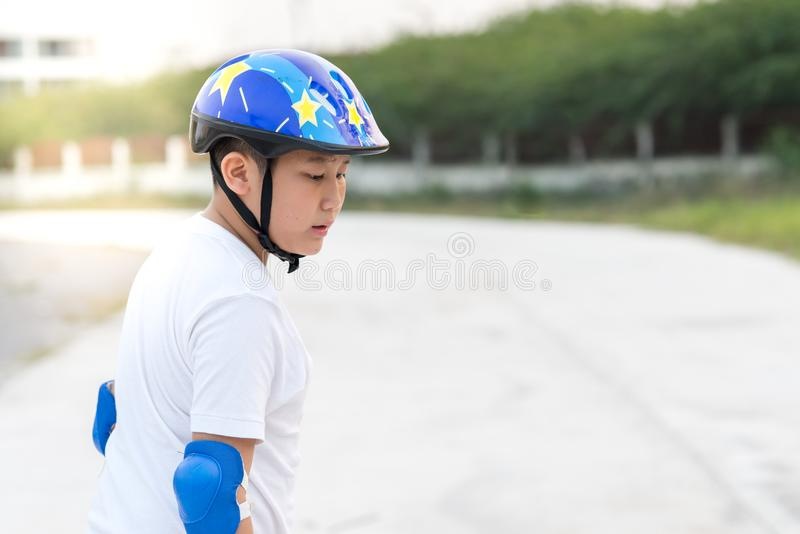 O menino que aprende a patinagem exterior, sua em sua cara fotos de stock