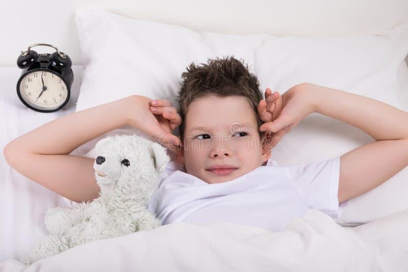 O menino que encontra-se na cama fecha suas orelhas do alarme foto de stock