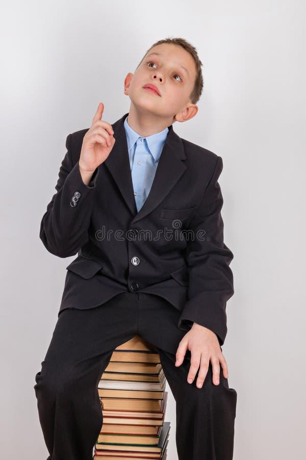 O menino que foi visitado pela ideia, senta-se em uma pilha de livros com um indicador aumentado imagem de stock