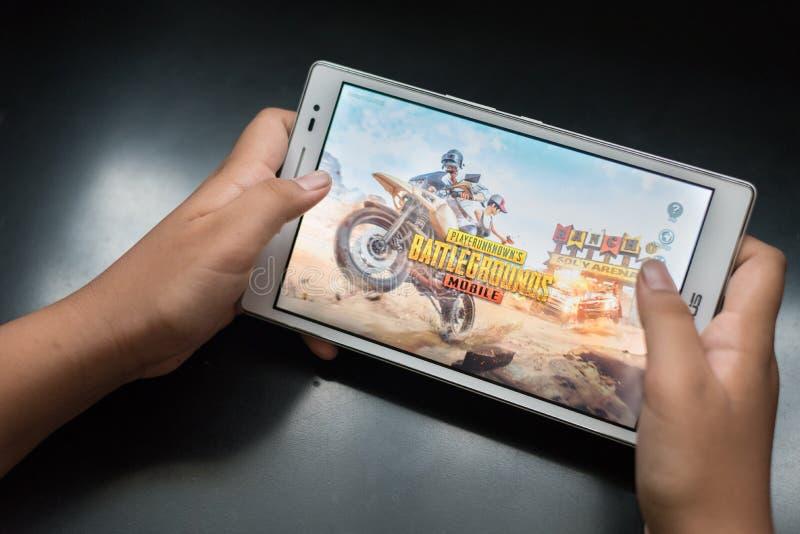 O menino que guarda uma tabuleta digital que joga o jogo móvel em linha chamou PUBG imagem de stock royalty free